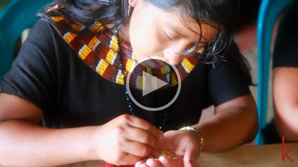 En konsthantverkare från en bergsby i Guatemala räknar pärlor till ett Wakami-armband