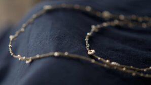 Ljusgrått halsband från Wakami med knutna silverdetaljer. Också snyggt som armband, virat flera varv runt handleden.